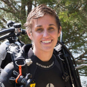 Young woman with short hair and scuba gear smiling