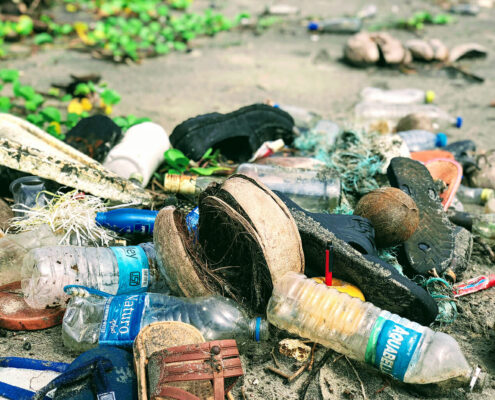 Plastic debris, including water bottles, shoes, and nets on a beach
