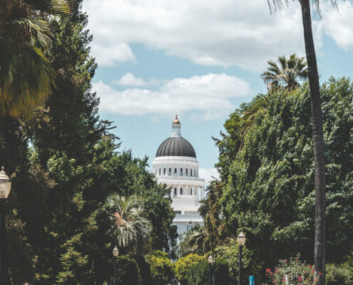View of the Sacramento Capitol Building down a street lined with trees, with a blue sky and light clouds behind the dome