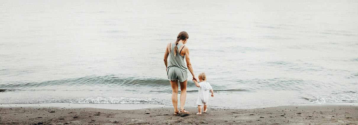 A woman and child walk on a beach towards the ocean