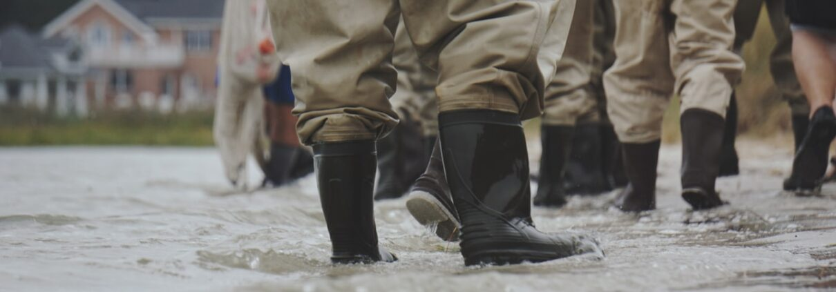 Several pairs of black rubber boots and brown waterproof pants face away from the viewer, standing ankle-deep in floodwaters
