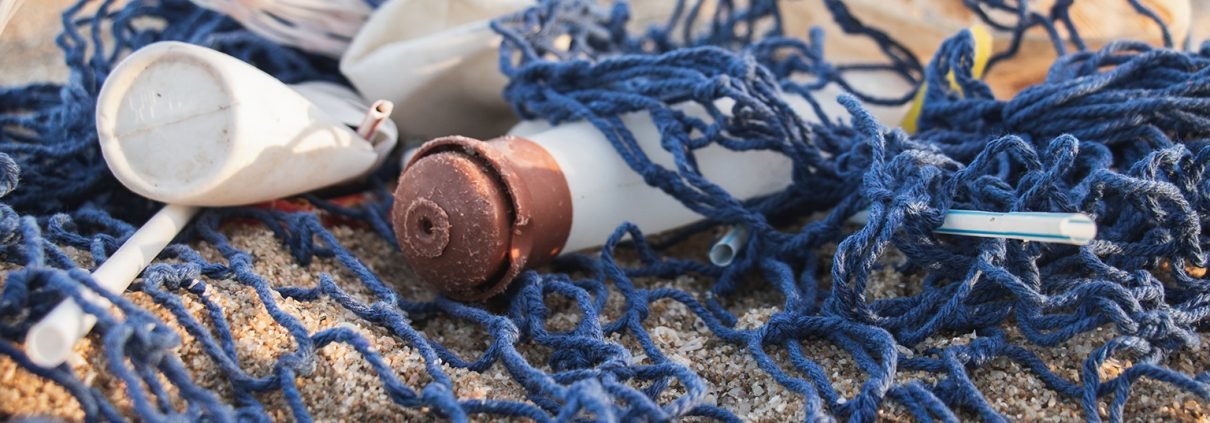 White and copper plastic bottles tangled in a net on the beach