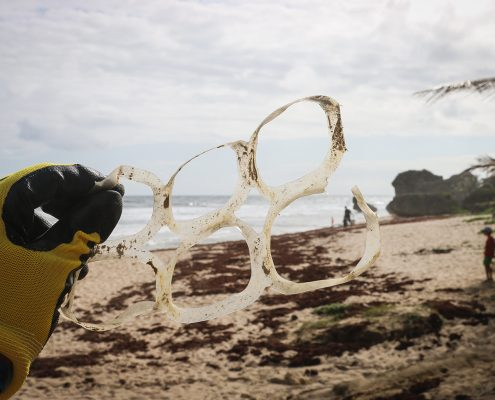 Gloved hand holding a set of dirty plastic pack rings on a cloudy beach