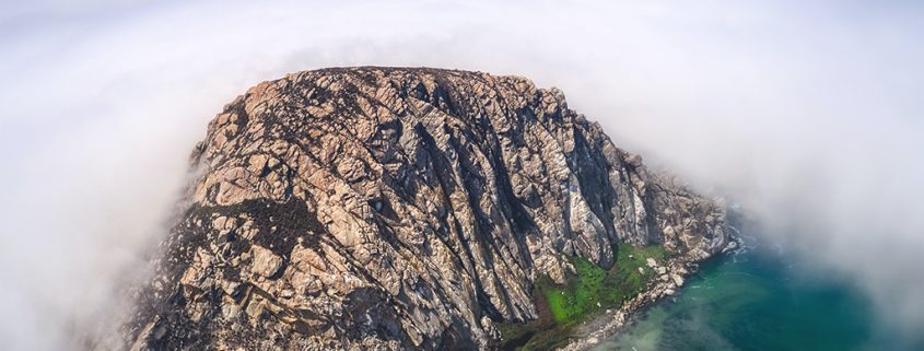Aerial photo of Morro Rock and the parking lot for Morro Bay surrounded by fog