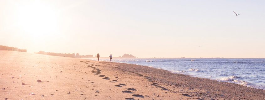 Photo of two silhouetted people walking along a beach in the morning, with the sun shining brightly into the camera. Their footprints are clearly visible on the sand of the beach.