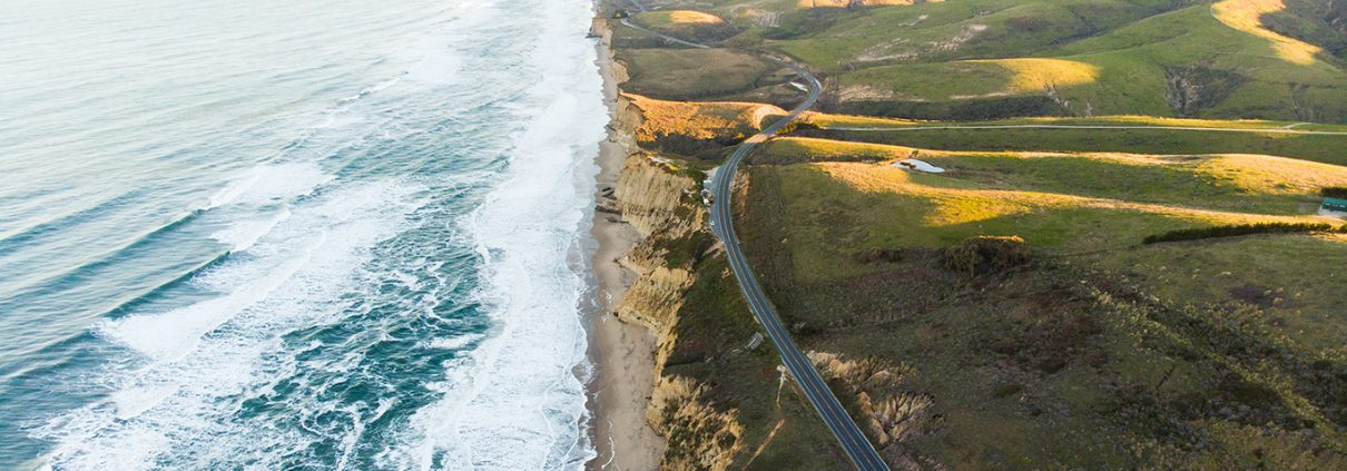Aerial photograph of CA Highway 101 and the coastline. Waves are visible in the water and green hills roll away to the east.