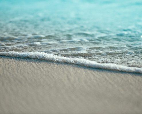 A close-up photo of sea foam on a white sand beach