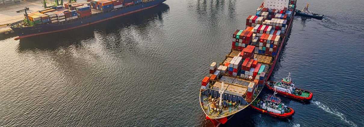 Three tugboats push a container ship in towards cranes in a port.